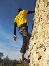 Young Man Climbs On A Rocky Wall