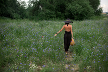 A Girl Walks Across The Field With Cornflowers And Tall Grass In The Evening In A Hat With A Wicker Basket. Summer Evenings In Nature