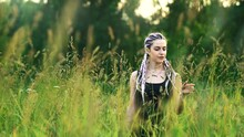 Young Modern Girl With Colorful Violet White Blue Braids. Braids, A Black T-shirt And Jeans. Stands In A Field Of Green Tall Grass. Enjoys The Nature. Depth Of Field. 4K Resolution