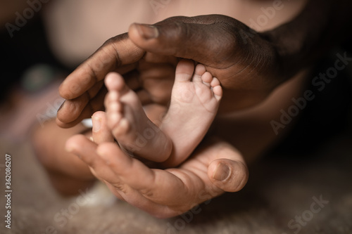 interracial family holding baby feet in hands mixed by black and white skin colo Fototapete