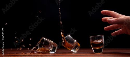 Valokuvatapetti Shot glass of whiskey tipping over
