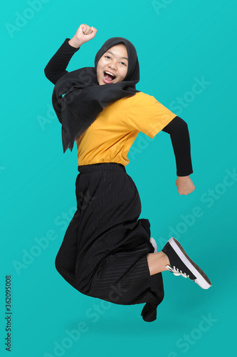 Full length body size view of Cute Asian teenager girl wearing headscarf jumping clench hands with a smile on her face Wallpaper Mural