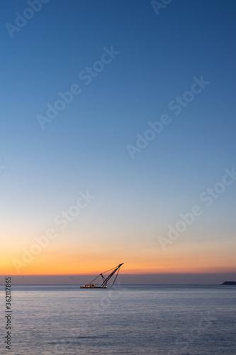 夜明けの空と海を航海するクレーン船 Fototapet