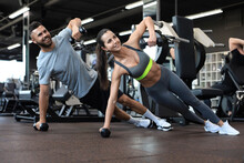 Strong Man And Woman Holding Dumbbells In Plank Position At The Gym.