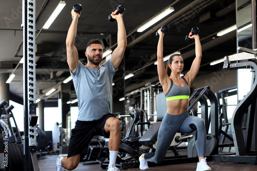 Obraz na plátně Attractive sports people are working out with dumbbells at gym.