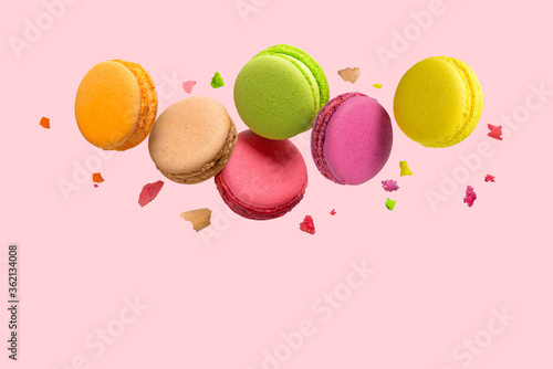 Fototapeta French macaroons cookies falls mixed with crumbs on pink background. Copy space. Flat lay, top view. obraz
