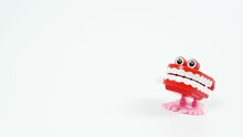 Chattering Teeth Toy Walks Into Focus On The Right Side, White Background