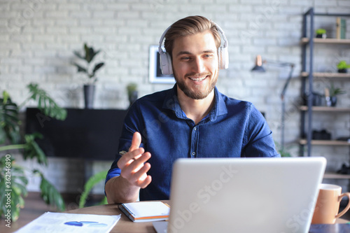 Confident man wearing headset speaking and watching business webinar training, listening to lecture Fototapeta