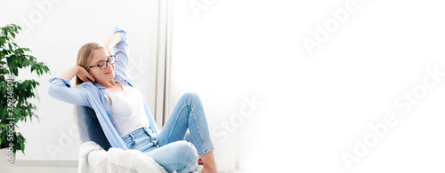 Obraz Young woman relaxing under air conditioner at home. Girl resting on couch, enjoying cool fresh air in cozy living room. White background, copy space. Self isolation, social distance in quarantine. - fototapety do salonu