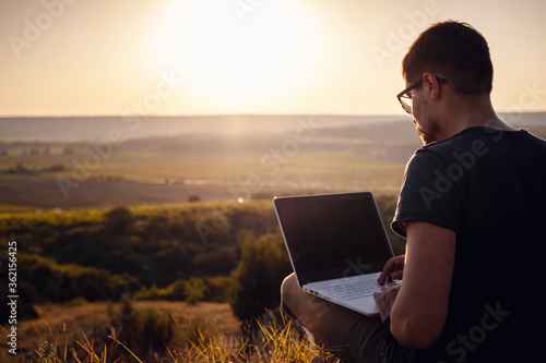 Valokuva man with laptop sitting on the edge of a mountain with stunning views of the val