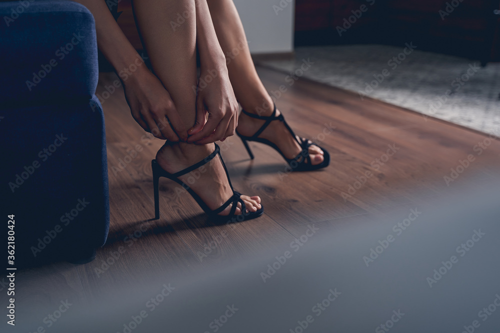 Fototapeta Young woman with beautiful legs taking off her shoes