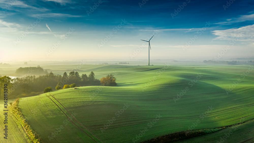 Foggy green field and wind turbine at sunrise, Poland