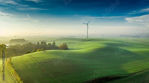 Fototapeta Foggy green field and wind turbine at sunrise, Poland obraz