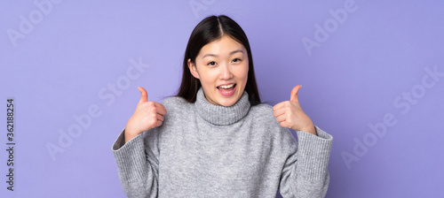 Obraz Young asian woman over isolated background giving a thumbs up gesture - fototapety do salonu