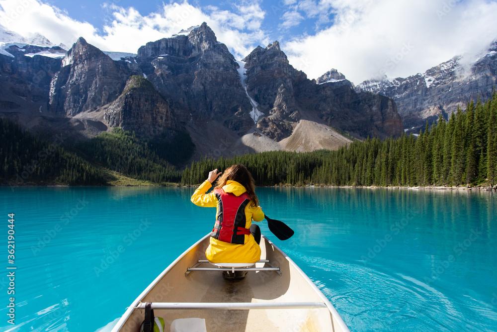Fototapeta Girl kayaking on a turquoise lake with a yellow rain jacket in summer