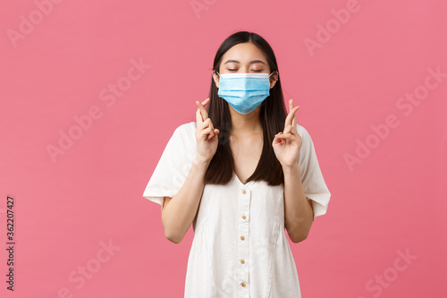 Fototapeta Covid-19, social distancing, virus and lifestyle concept. Hopeful dreamy asian girl making wish, close eyes and smiling in medical mask, cross fingers good luck, pleading over pink background obraz