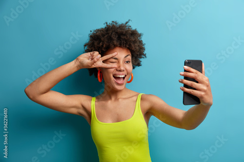 Fototapeta Playful positive curly haired woman makes peace sign over eye, takes selfie on smartphone, shows lucky peace gesture, wears casual clothes. Happy female blogger records vlog online, says hey followers obraz