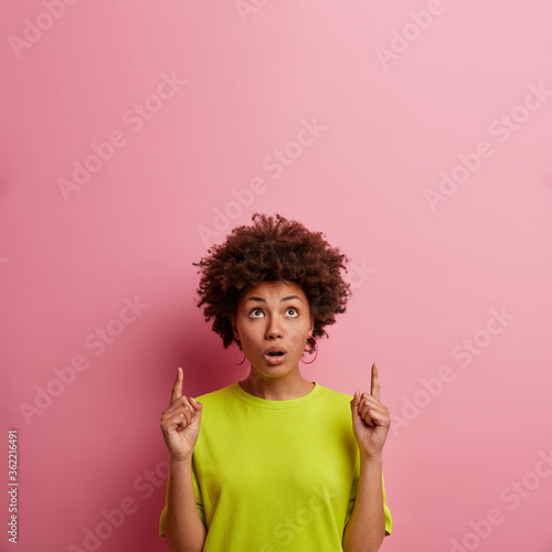 Fotografia, Obraz Unbelievable advertise is here! Surprised woman with Afro hair points above and
