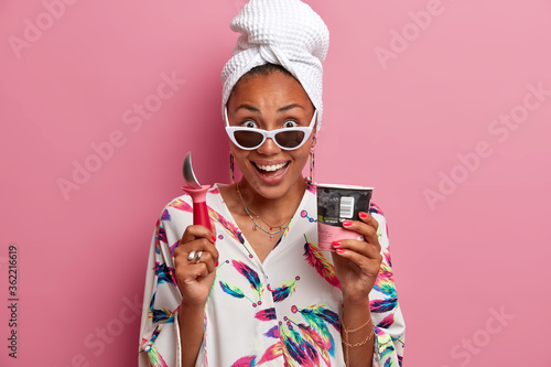 Fototapeta People, summer mood and nutrition concept. Happy stylish woman eats cold ice cream, holds spoon, smiles pleasantly, wears sunglasses, dressed in domestic clothes with jewelry, enjoys pleasant taste obraz