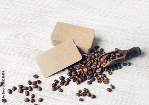 Cuadros en Lienzo Coffee beans and kraft paper business cards over light wood table background