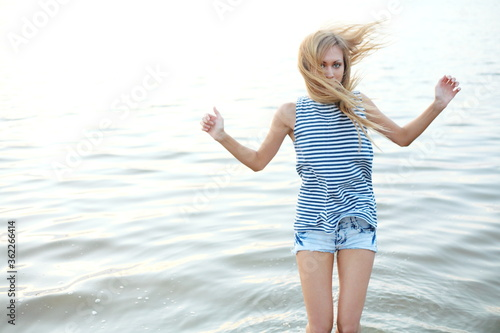 Fotografie, Tablou Blond haired woman is standing in the water, her hair is windswept