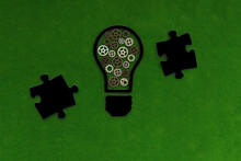 Electric Light Bulb, Iron Gears In Black On A Green Background. Business Ideas, Creative Thinking. Creation.