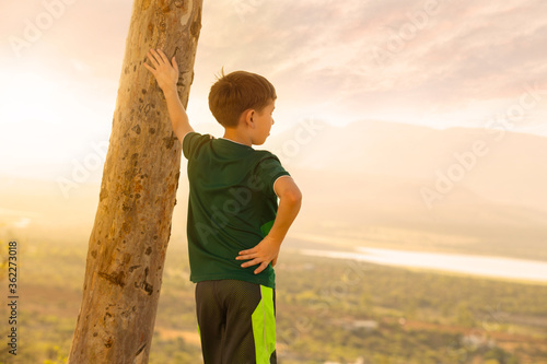 Fotografia, Obraz young boy standing on the edge of a cliff