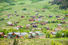 Mount Crested Butte Near Gunnison, Colorado Village Town Houses In Summer With Many Wooden Lodging Buildings On Hillside With Green Lush Color Grass