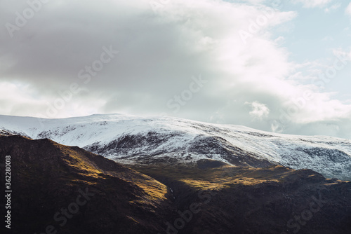 Fototapeta Atmospheric view to snowy mountains in sunlight under cloudy sky