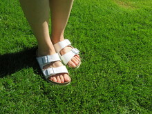 Closeup Photo Of Woman Feet In White Sandals Walking On Grass During Summer