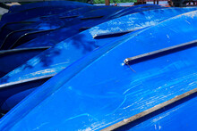 A Row Of Bright Blue Rowboats On The Shore