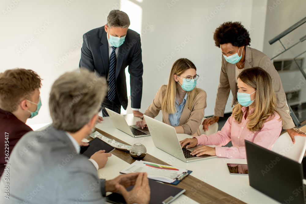 Fototapeta Group business people have a meeting and working in office and wear masks as protection from corona virus
