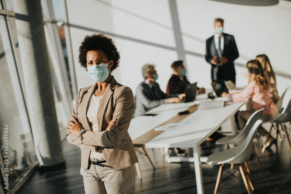 Fototapeta African American woman standing in office and wear mask as protection from corona virus