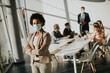 canvas print picture - African American woman standing in office and wear mask as protection from corona virus