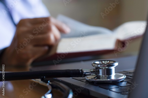 Fototapeta Female doctor reading text boo with  medical stethoscope on the desk in room at clinic