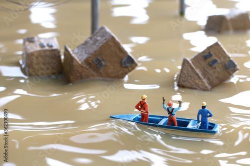 Photo 水害によって水浸しになった街と助けを求める人々のジオラマ