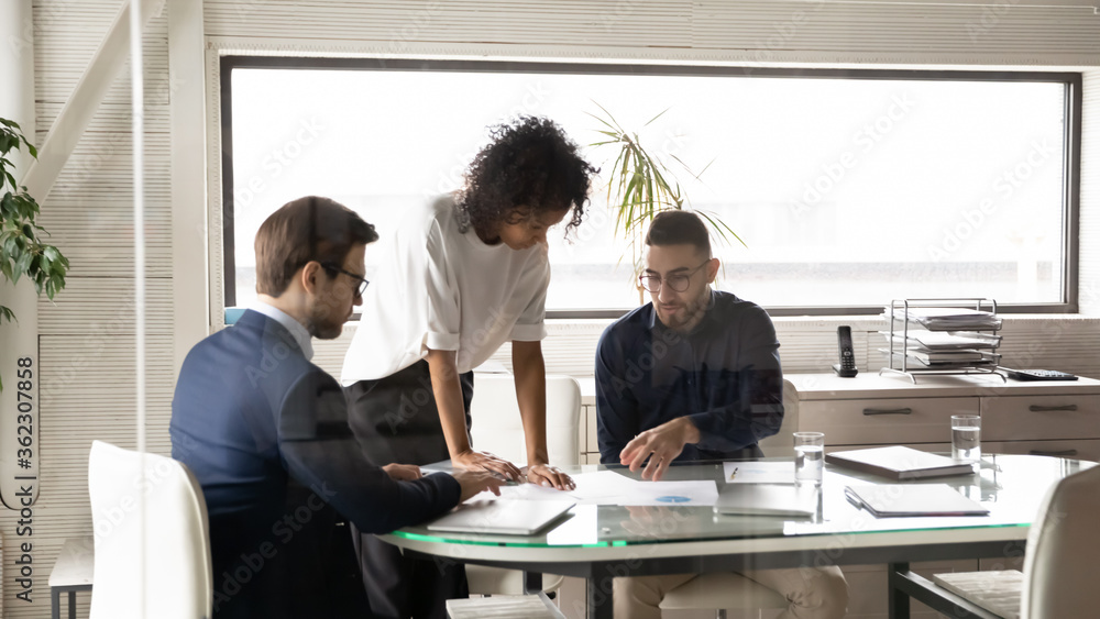 Fototapeta Diverse multiethnic businesspeople brainstorm discuss company financial paperwork at boardroom meeting together, multiracial colleagues talk consider paper documents at team briefing in office