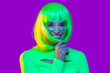 Leinwanddruck Bild - Happy teen girl dressed in green neon top, glitter on cheeks, smiling and laughing at party, isolated on purple background