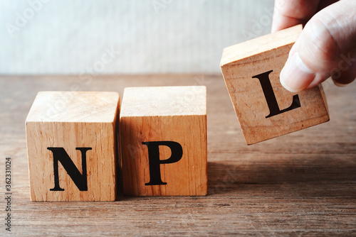 Fototapety, obrazy: Hand pick up wood cube block which hace text NPL, economic business concept.