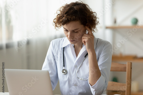 Pensive young female nurse in white medical uniform work on laptop thinking pondering, thoughtful Caucasian woman doctor busy using computer in hospital or clinic, make decision or analyze results