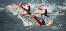 Competitors Swimming Out Into Open Water At The Beginning Of Triathlon