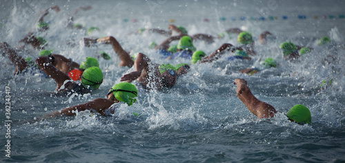 Fotografiet Competitors swimming out into open water at the beginning of triathlon