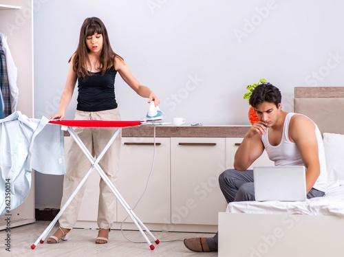 Young woman doing ironing for her husband