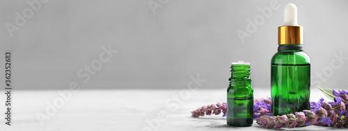 Fototapeta Bottles of essential oil and flowers on table, space for text. Banner design obraz