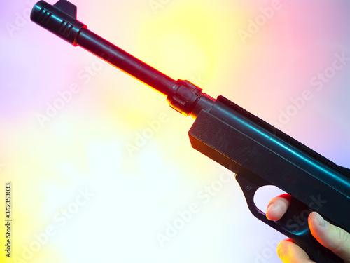 Obraz na plátně Closeup photo of the fingers on the trigger of an old black Soviet revolver on a