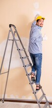 Young Contractor Sanding Wall ...