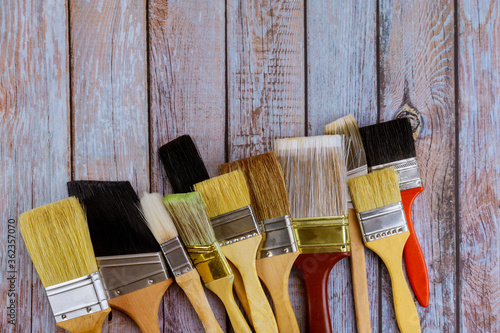 Fototapeta Painter work table renovation painting different size paint brushes on wood background obraz