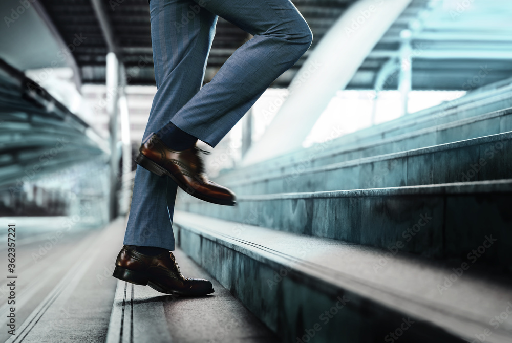 Fototapeta Motivation and challenging Concept. Steps Forward into a Success. Low Section of Businessman Walking Up on Staircase