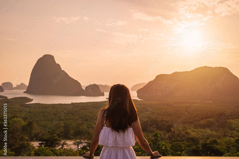 Fototapeta Young woman traveler looking at sunrise over the mountain at samet nang she, Thailand