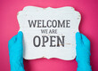 Leinwanddruck Bild - Welcome we are open wooden sign in hands with blue medical gloves. Cafe, restaurant and shop reopen after COVID -19 coronavirus pandemic.